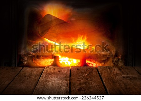 Fireplace and old vintage planked wood table in perspective. Burning firewood and flames as background. - stock photo