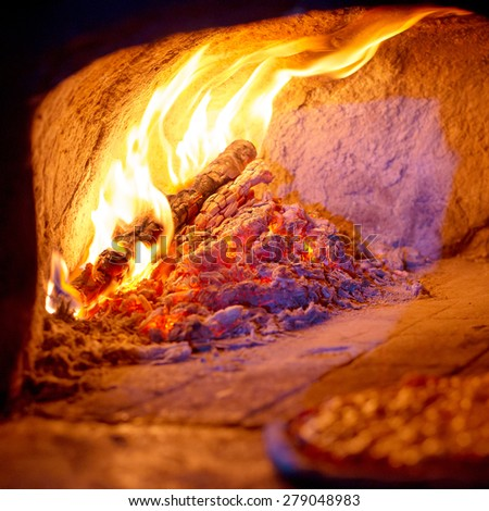 Fireplace burning. Warm burning and glowing fire in traditional brick oven - stock photo