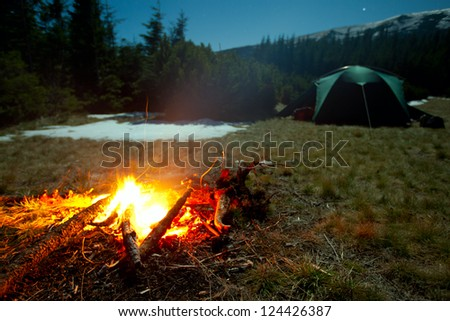 Fireplace during rest near tent at night - stock photo
