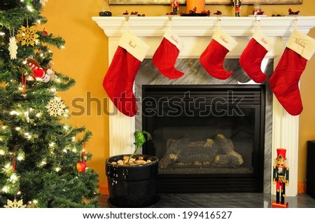 Fireplace, Lit Christmas tree with ornaments, and stockings make for a holiday spirit filled with joy - stock photo