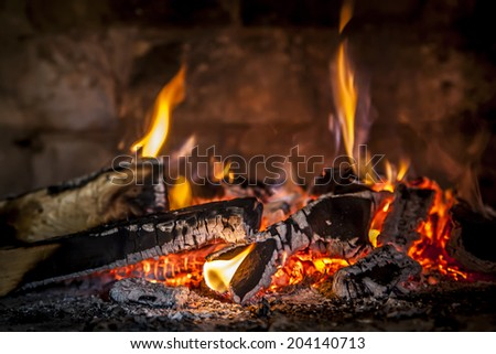 Fireplace with a blazing flames, relaxing view of the fire, wall of bricks in the background. - stock photo