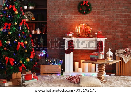 Fireplace with beautiful Christmas decorations in comfortable living room - stock photo