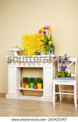 Fireplace with beautiful spring decorations in room - stock photo
