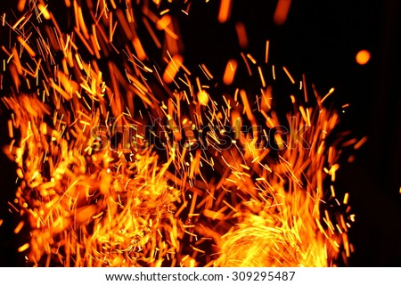Firestorm texture. Bokeh lights on black background, shot of flying fire sparks in the air - stock photo