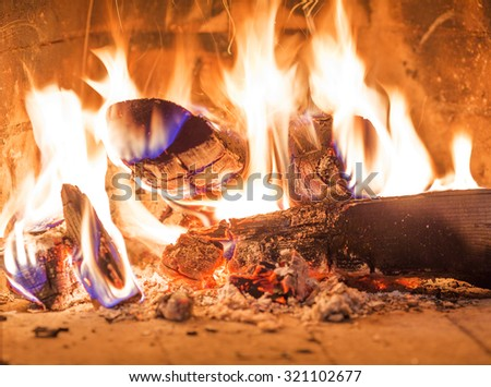 Firewood burning in fireplace fire red ashes heat - stock photo