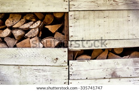 Firewood stacked in wooden hut - stock photo