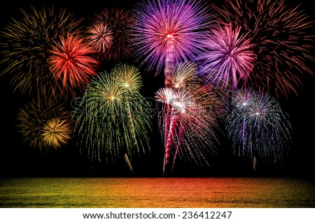 Firework celebration from the sea shore. - stock photo