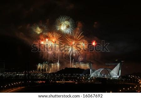 Fireworks are being displayed over Malaysia's landmark Seri Saujana Bridge in Putrajaya, Malaysia. - stock photo
