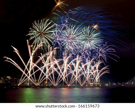 Fireworks,colorful fireworks background,fireworks explosion in dark sky with city sillouthe and colorful reflect on water,fireworks in Riga,Latvia,long exposure fireworks,Independence, explode concept - stock photo