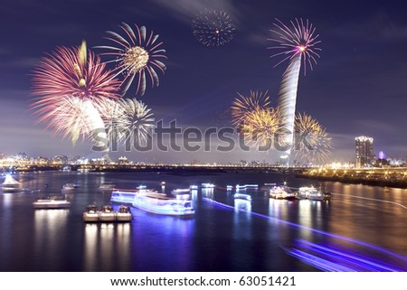 Fireworks firing up into the sky with a boat on a river below them, with a reflection on the water - stock photo