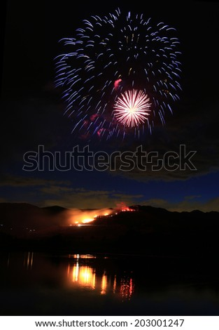 fireworks with a fire burning on a hill below, Midway, Utah, USA. - stock photo