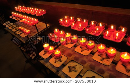 Firing yellow candles in red chandeliers giving red reflections to church wall - stock photo