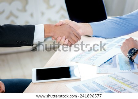 Firm handshake. Two serious businessman sitting at the negotiating table in the office and shake hands. Business people dressed in formal wear - stock photo