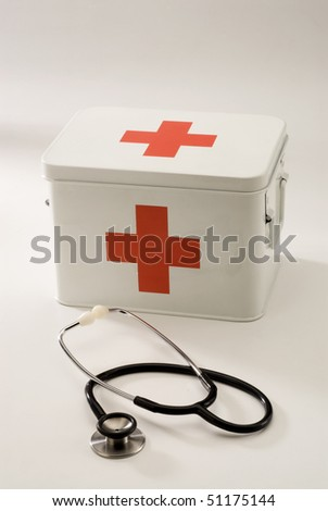 First aid box in white background and a stethoscope in foreground. - stock photo
