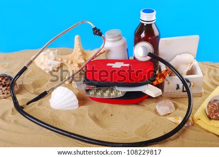 first aid box with medicines,thermometer and stethoscope on the beach as healthy summer holiday concept - stock photo