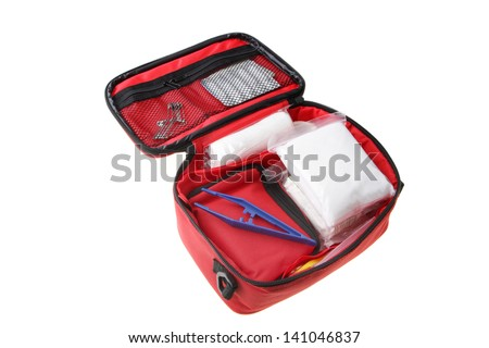 First Aid Kit showing bandages, tweezers; safety pins in a red soft case isolated on white background. - stock photo