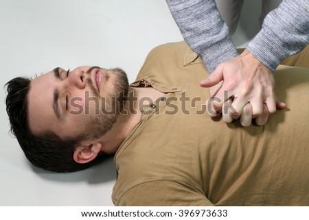 first aid - man doing a cardiopulmonary resuscitation  - stock photo