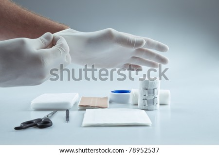 First aid medical supplies and a doctor putting on protective gloves - stock photo