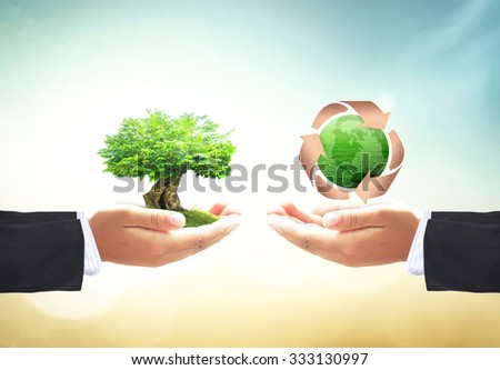 First, Businessman hands holding big tree. Second, holding recycle arrow symbol made of old paper texture protecting green earth globe of grass over blurred nature. Saving world environmental concept. - stock photo
