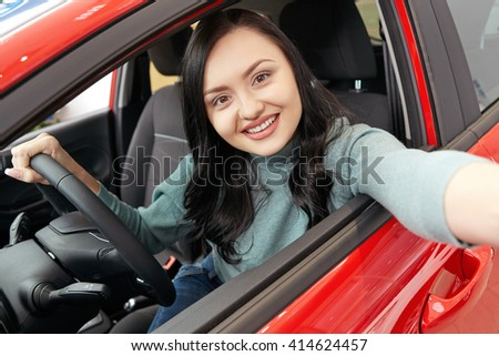 First car selfie. Gorgeous cheerful female sitting in her new car making a selfie with her phone - stock photo