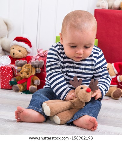 First Christmas: baby unwrapping a present - playing with a plush animal - stock photo