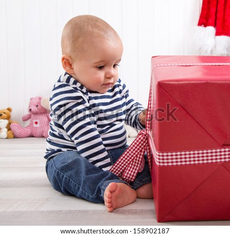 First Christmas: baby unwrapping a red present with a red checkered ribbon - cute little boy - stock photo