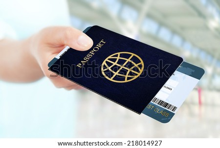 first class flight ticket and passport holded by hand. focus on ticket and passport - stock photo