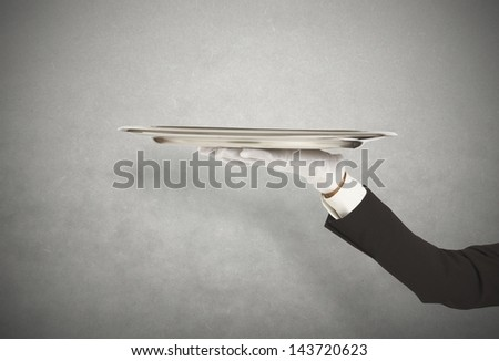 First-class service with waiter holding the tray - stock photo