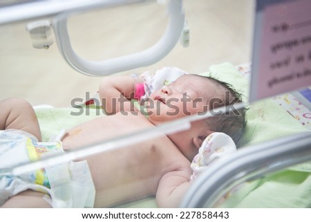 first day of asian newborn baby in Incubator care at nursery hospital - stock photo