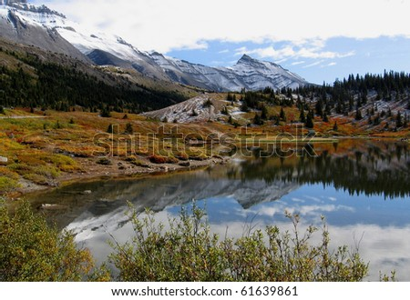 First fall snow at small lake near columbia icefield in Canadian Rockies (Jasper/Banff National Park). - stock photo