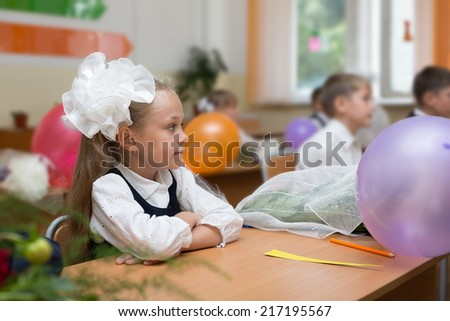 First grader girl in the first day of school in the classroom. Russia.  - stock photo