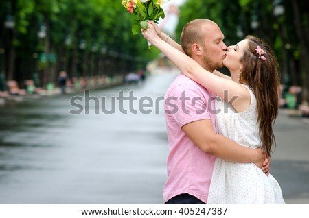 First kiss. Young couple of lovers in love passionately kissing standing on path in summer park. - stock photo