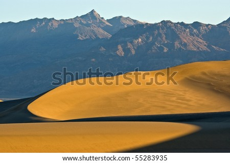 First light hits the sand dunes on Mesquite Flat showing curved patterns of light and shadows underneath towering mountains in Death Valley National Park, California. - stock photo