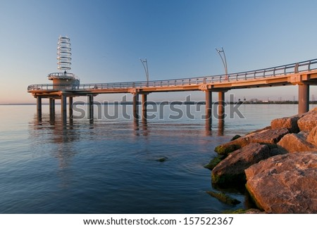 First light throws nice color on a newly constructed pier in Lake Ontario - stock photo