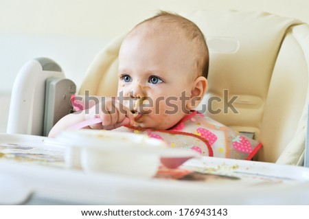 first meal of six months baby on her face and everywhere - stock photo