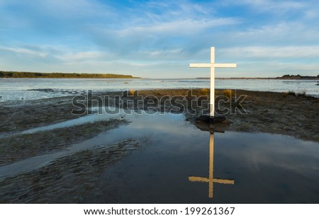 First morning sunlight on this white cross. - stock photo