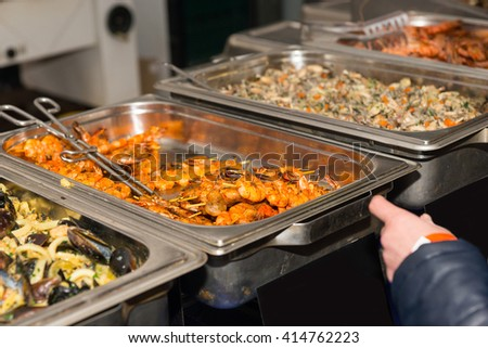 First Person Perspective of Customer Perusing Offerings at Restaurant Buffet or Food Festival, Pausing in front of Steamer Tray with Grilled Shrimp Skewers - stock photo