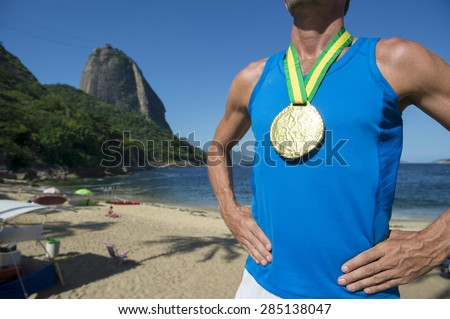 First place athlete wearing gold medal standing outdoors in front of Sugarloaf Mountain Rio de Janeiro Brazil  - stock photo