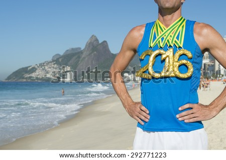First place athlete wearing 2016 gold medals standing outdoors on Ipanema Beach in Rio de Janeiro Brazil  - stock photo