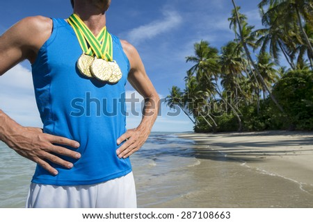 First place Brazilian athlete standing with gold medals on empty beach - stock photo