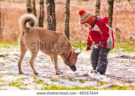 First snow. Little boy playing with his dog. - stock photo