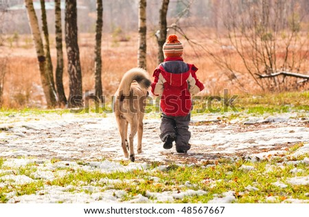 First snow. Little boy walking with his dog. - stock photo