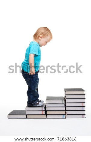 First steps of education - kid on steps made of books - stock photo