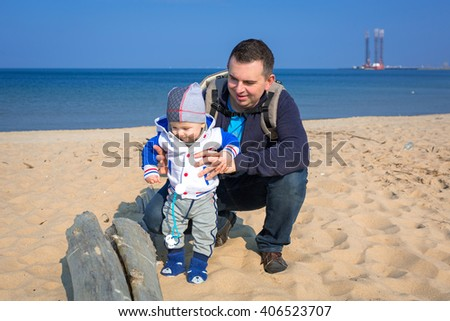 First steps of little baby boy with his father at the beach - stock photo