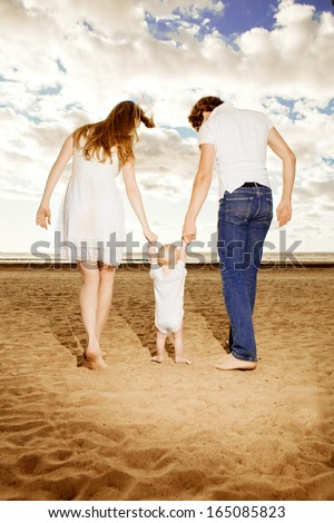 First steps of the kid. Happy family is helping baby takes first steps on the beach - stock photo