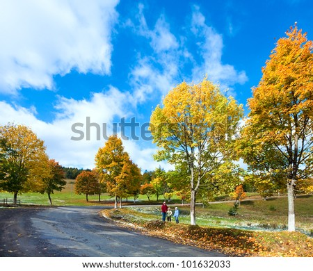 First winter snow and autumn colourful foliage near mountain secondary road (and mother with children) (Carpathian, Ukraine) - stock photo