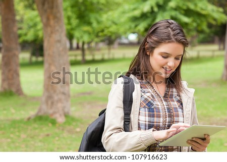 First-year student using a touch pad in a park - stock photo