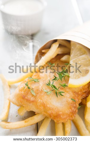 Fish and chips. Fried fish fillet with french fries wrapped by paper cone, on wooden background. Fresh cooked with hot steams. - stock photo