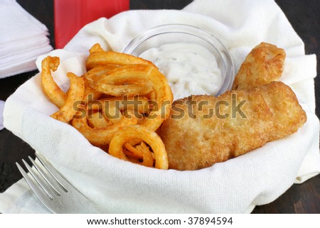 Fish and Chips in a napkin lined basket on an old wooden table. - stock photo