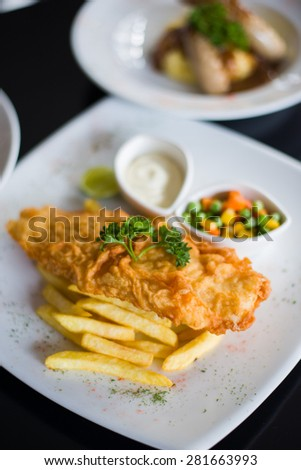 fish and chips served with tartar sauce and vegetables - stock photo
